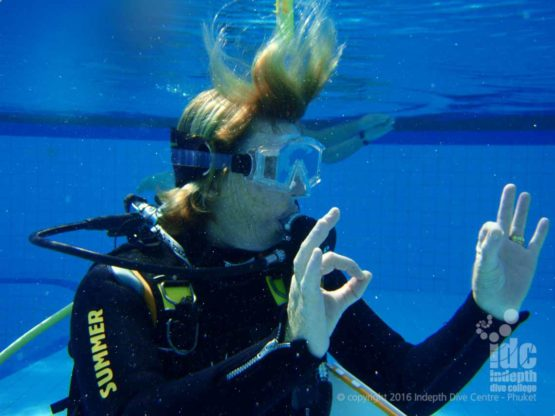 PADI Scuba Instructor signals OK to her students in the pool